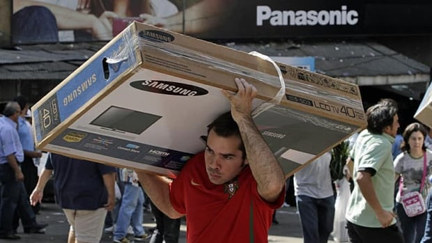 A man carries home his recent LCD television purchase. A BMO-sponsored poll released Tuesday shows men spend more on impulse buys than women do.