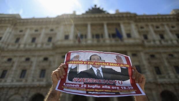 "A demonstrator holds a poster of Silvio Berlusconi reading ""Nobody is more equal than the others, not even you,"" outside Italy's Supreme Court, which is hearing the former prime minister's appeal of a tax fraud conviction."