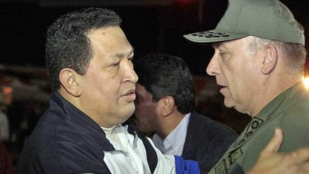 Venezuela's President Hugo Chavez, left, talks to Venezuela's Defence Minister Admiral Diego Molero on arrival from Cuba at Simon Bolivar airport in Caracas Friday. Chavez made a theatrical return from Cuba on Friday after medical treatment, walking and joking in a first public appearance for three weeks that quashed rumours he may have been at death's door.