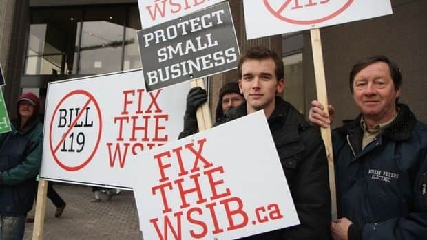 Justin Dokter, centre, and fellow workers protested on King Street Tuesday against stricter rules for workplace insurance.