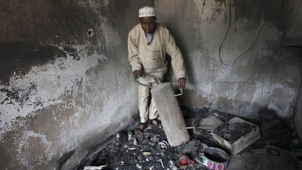An unidentified official displays burnt equipment inside a prison in Bauchi, Nigeria.