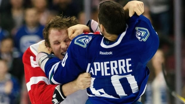 Justin Abdelkader, left, of the Red Wings and Maxim Lapierre of the Canucks tussle on Feb. 2.