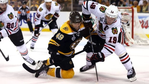 Rich Peverley (49) of the Boston Bruins tries to handle the puck against Chicago Blackhawks captain Jonathan Toews in Game 4 at TD Garden on Wednesday in Boston.