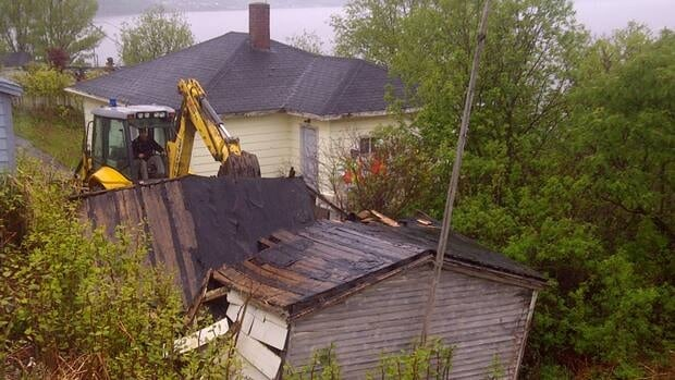 Heavy equipment was used Friday to tear down a shed that had been home to scores of cats.