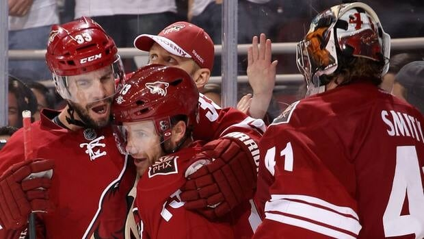 Ray Whitney, centre, of the Phoenix Coyotes celebrates with Adrian Aucoin, left, and goaltender Mike Smith after Whitney scored the overtime goal on Friday.