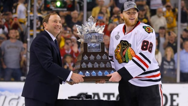 Chicago Blackhawks' Patrick Kane, right, accepts the Conn Smythe trophy given to the NHL playoffs' most valuable player from NHL Commissioner Gary Bettman after winning the Stanley Cup on Monday.