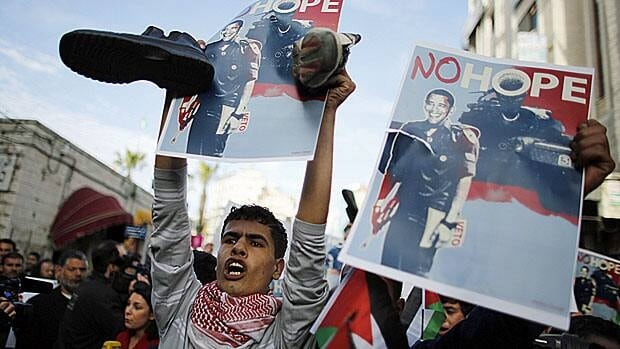 A Palestinian man holds shoes, a symbol of disrespect, and a placard of U.S. President Barack Obama during a protest in the West Bank city of Ramallah earlier today.