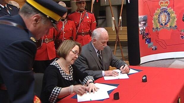 B.C. Justice Minister Shirley Bond and federal Public Safety Minister Vic Toews sign the new B.C. RCMP contract on March 21. Several B.C. politicians say they are surprised to learn the RCMP are receiving pay raises.