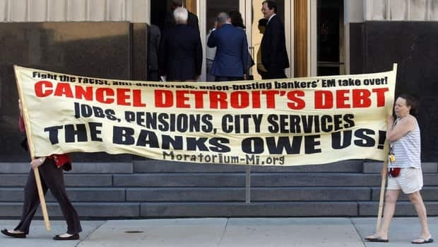 Protesters carry a banner calling for Detroit's debt to be cancelled as people enter the federal courthouse for the city's municipal bankruptcy hearings Wednesday.