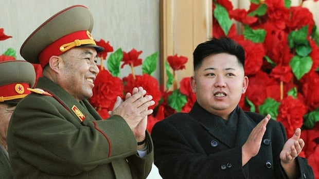 North Korean leader Kim Jong-un, right, and General Staff Chief Ri Yong Ho clap as they review a parade of thousands of soldiers. State television reported Sunday that Ri has been dismissed due to illness, though skeptics have noted that the influential mentor to Kim seemed healthy in recent appearance.