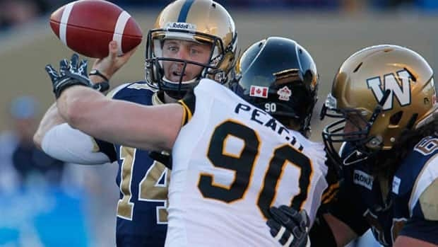 Winnipeg Blue Bombers quarterback Joey Elliott throws despite pressure from Hamilton's Greg Peach at a game in August, 2012.