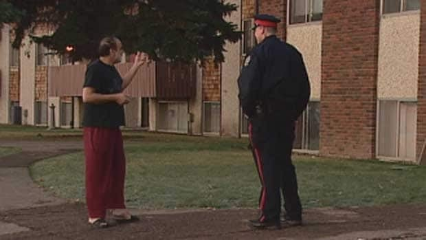 A man speaks to a police officer outside the Westlawn Village apartment building on Friday morning. A fire on Thursday evening caused $1.8 million in damages.
