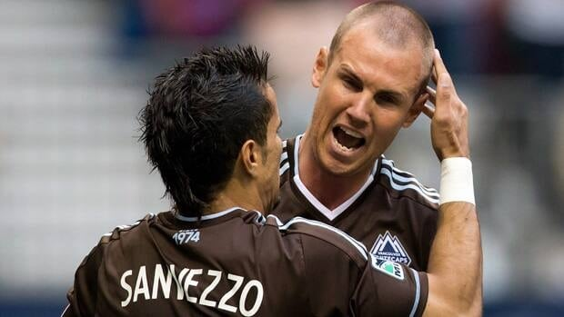Vancouver Whitecaps player Camilo Sanvezzo, left, celebrates with Kenny Miller, during Saturday's win.