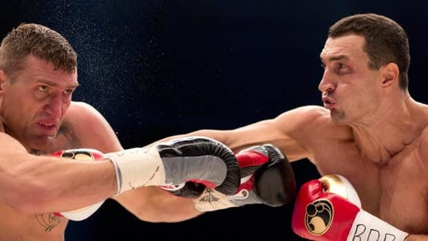 WBA, IBF and WBO heavyweight boxing world champion Wladimir Klitschko, right, lands on Mariusz Wach of Poland in Saturday's bout in Hamburg.