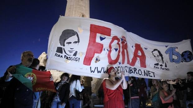 Protesters in Lisbon hold a banner calling for the ouster of Prime Minister Pedro Passos Coelho and former foreign minister Paulo Portas. The country's political crisis over austerity measures has put the stock market into a nosedive and brought bond interest rates up.
