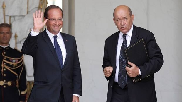 French President Francois Hollande, left, waves to the media as he leaves a Cabinet meeting  with Defense Minister Jean-Yves Le Drian at the Elysee Palace in Paris.