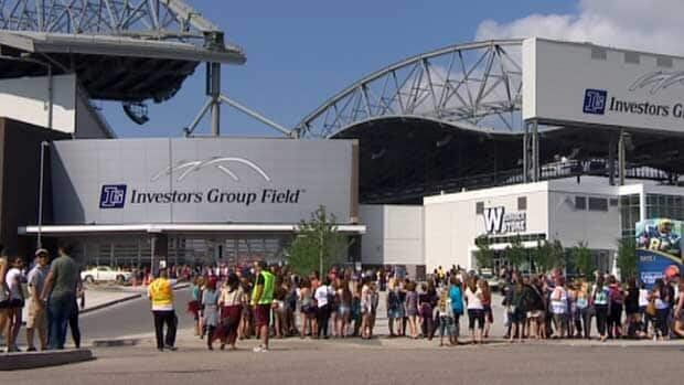 People attending the Taylor Swift concert in Winnipeg stand outside Investors Group Field before the show on Saturday.