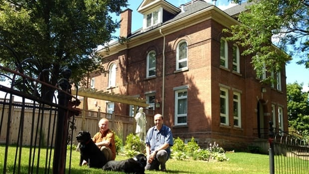 Father Tony O'Dell, left, Father Jarek Pachocki and dogs have been moved into the long-empty rectory behind them. The statue is a freshly-restored St. Lawrence.