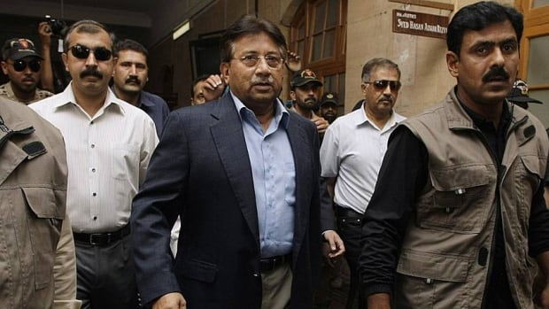 Former Pakistani President Pervez Musharraf, center, surrounded by guards arrives in a court in Karachi, Pakistan on Friday.