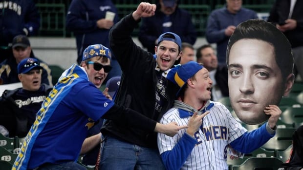 In this April 2013 file photo, Fans hold up a giant photo of Ryan Braun before the the Milwaukee Brewers take on the Colorado Rockies. Braun finally admitted to using perfromance-enhancing drugs Thursday after he was suspended last month.