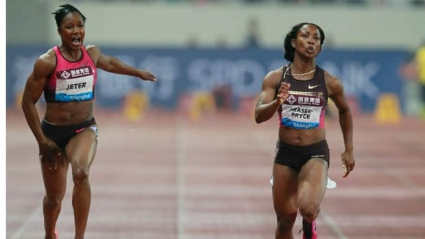 Carmelita Jeter, left, grimaces in pain as Shelly-Ann Fraser-Pryce, right, sprints to victory in the women's 100 metres at the Diamond League track and field meet Saturday in Shanghai.