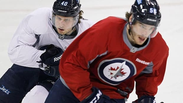 Winnipeg Jets' Maxime Macenauer (left) and Zach Redmond (59) skate during training camp in Winnipeg in January 2013.