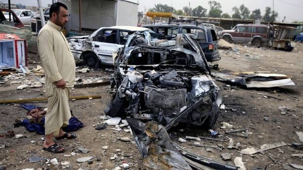 An Iraqi man inspects the aftermath of a car bomb attack at a used cars dealers parking lot in Habibiya neighbourhood of eastern Baghdad on Tuesday.