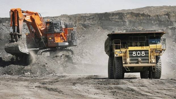 A truck drives away from a mining shovel at the Shell Albian Sands oilsands mine near Fort McMurray, Alta. The Canadian ambassador to the European Union has threatened to complain to the WTO if the EU designates oilsands crude as more polluting than conventional oil.