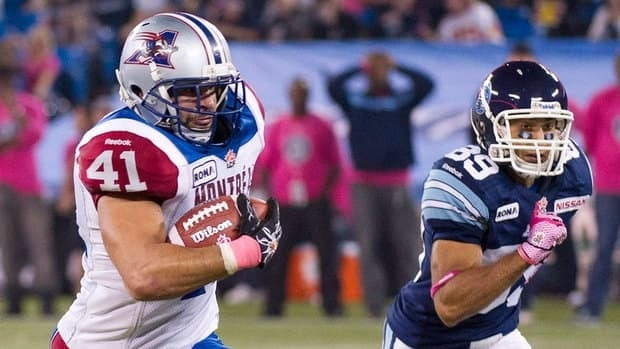 Alouettes' Shea Emry, left, runs back an interception for a touchdown against the Argonauts on Sunday.