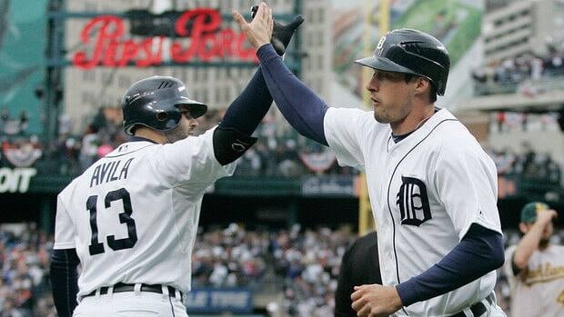 Tigers' pinch runner Don Kelly, right, is met at the dugout by teammate Alex Avila after scoring on a wild pitch in the eighth inning. Kelly delivered the winning hit in the ninth, a bases-loaded sacrifice fly.