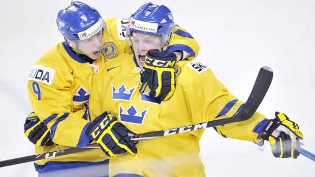 Sweden's Max Friberg is congratulated by teammate John Klingberg after scoring the tying goal against Finland during the semifinal match against Finland.