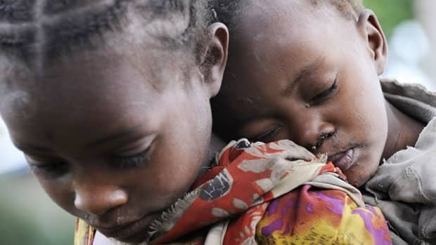 A girl carries her brother as she waits for food distribution in Buge village, Wolayita region in southern Ethiopia in this 2008 photo released by the International Federation of Red Cross and Red Crescent Societies (IFRC). New York-based Human Rights Watch has called on Canada and other donor countries to put pressure on the African country to stop evicting villagers to use the land for corporate interests.