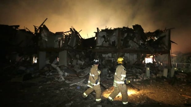 Firefighters check a destroyed apartment complex near the fertilizer plant that exploded in West, Texas, on Thursday, April 18, 2013.