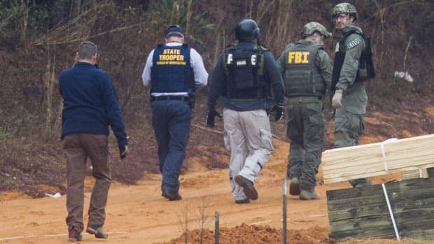 FBI agents and Alabama State Troopers work together near the site of the bunker where a nearly week-long standoff with Jimmy Lee Dykes ended on Monday.