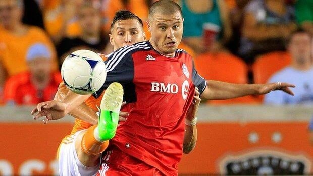 Houston Dynamo's Geoff Cameron, left and Danny Koevermans of Toronto FC fight for the ball in the first half on Wednesday.