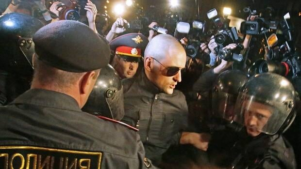 Police officers detain opposition leader Sergei Udaltsov, in sunglasses, after a protest rally in Moscow in September.