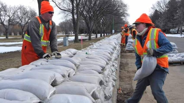 Workers pile sandbags onto a dyke along the south side of Wascana Creek in Regina. Residents of 340 homes there have been told to be ready to leave.