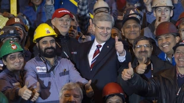 Canadian Prime Minister Stephen Harper poses with workers after announcing a new deal to build non-combat ships for the Coast Guard and Royal Canadian Navy at the Seaspan shipyards in North Vancouver, B.C., on Jan. 12, 2012. B.C. was one of only three provinces that saw overall job growth above one per cent between January 2011 and January 2012.