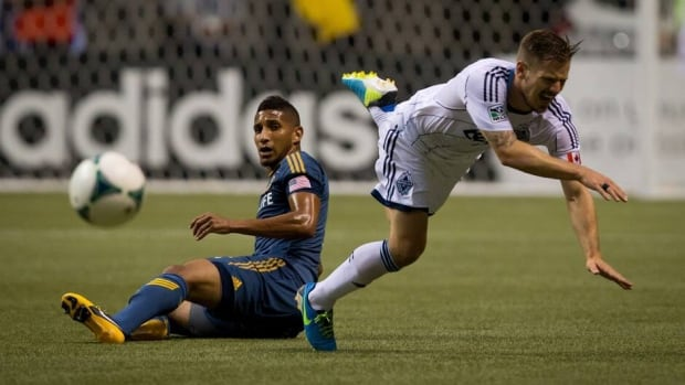 Vancouver Whitecaps' Jordan Harvey, right, is tripped up by Los Angeles Galaxy's Sean Franklin during the second half Saturday.