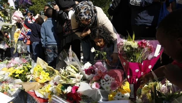 Zainab Sheikh, a member of Muslim group Minhaj-ul-Quran, and her daughter Rabeea Sethi, 3, lay flowers in memory of British soldier Lee Rigby at the scene of his murder in Woolwich, southeast London on Monday.