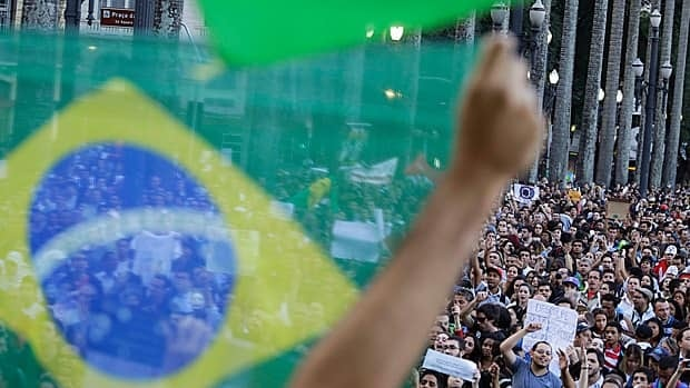A demonstrator holds up a Brazilian flag in front of a group of protestors gathered in the main plaza of Sao Paulo on Tuesday, as some of the biggest demonstrations since the end of Brazil's 1964-85 dictatorship have broken out.