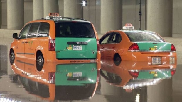 A pair of Beck taxi cabs carrying several passengers became trapped in a downtown Toronto underpass after heavy rain on Tuesday night.