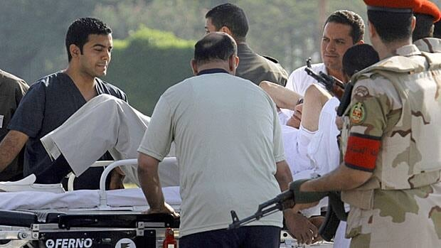 Egyptian medics and military policemen escort former president Hosni Mubarak, 85, after after he was flown by a helicopter ambulance to the Maadi Military Hospital from Torah prison on Thursday.