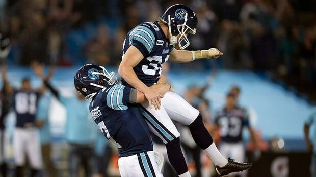 Toronto Argonauts kicker Swayze Waters, right, leaps into the arms of quarterback Trevor Harris after kicking the game winning field goal in the last second of CFL action against the Hamilton Tiger-Cats in Toronto on Thursday November 1, 2012.