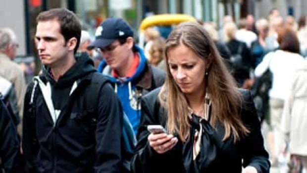 A businesswoman checks her smartphone while crossing the street. Mobile technology is making for a lot of unpaid overtime, experts say.