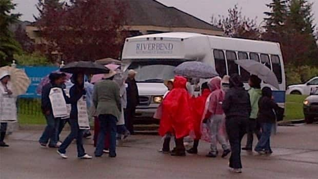 Staff walk the picket line in the rain at Revera Riverbend Retirement Living on Tuesday morning. They had not yet been told that the province ended their strike by sending the dispute to binding arbitration.