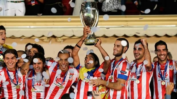Atletico Madrid striker Falcao holds the UEFA Supercup with his teammates after defeating Chelsea in the final on Friday.