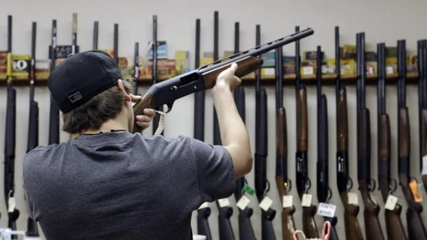 A customer checks out a shotgun at Burdett & Son Outdoor Adventure Shop in College Station, Texas, in Dec. 2012. The divide between those who favour gun control and those who don't has existed for decades, separating America into hostile camps.