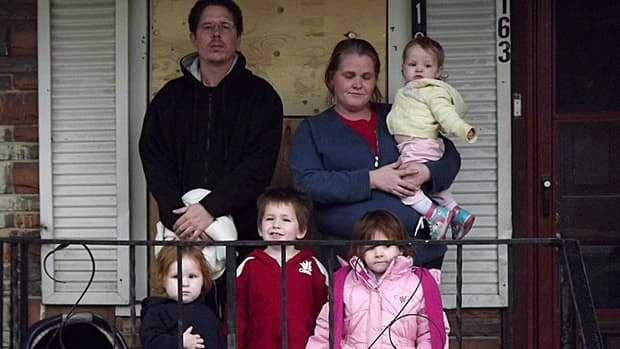 On the porch of their burned-out home is (back row, from left) Ron Wong, Melissa Ryerse, Lexi, (front row, left to right) Avery, Kailem and Zaysha. Not shown: six-month-old Gabe. (Paula Fancey)