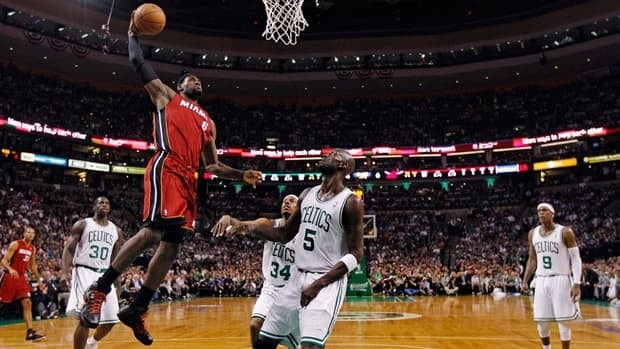 Miami Heat forward LeBron James, left, goes for a dunk past Boston Celtics' Kevin Garnett (5) during the first half in Game 6 on Thursday.